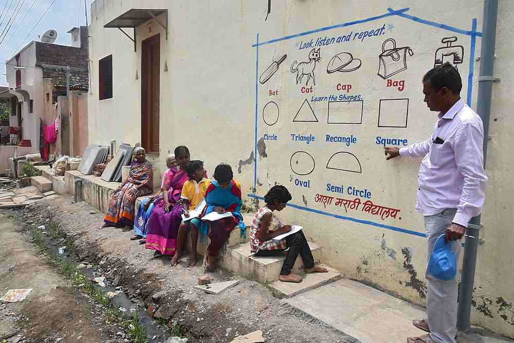 Kalidas Chavdekar, a school teacher of Aasha Marathi Vidyalay points to a writing from textbooks of various subjects painted on the wall of a house to teach students. — AFP pic