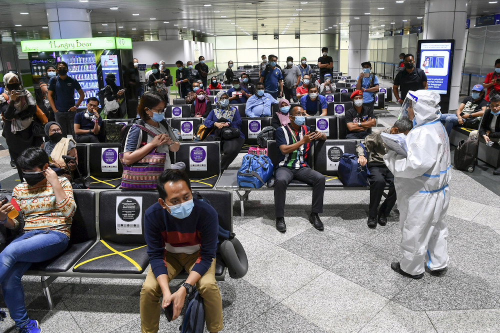 Health Ministry officers briefing passengers from Sabah upon their arrival at the Kuala Lumpur International Airport (KLIA) September 28, 2020. — Bernama pic