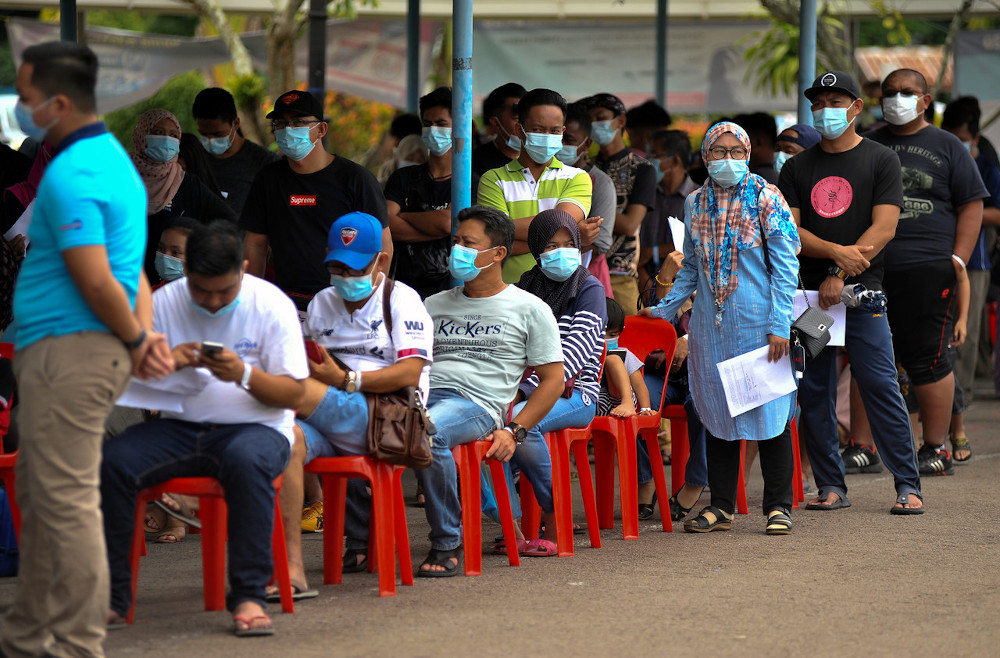People returning from the mainland wait for their turns for the Covid-19 and Polymerase Chain Reaction (PCR) tests at the Membedai Health Clinic in Labuan, September 29, 2020. — Bernama pic