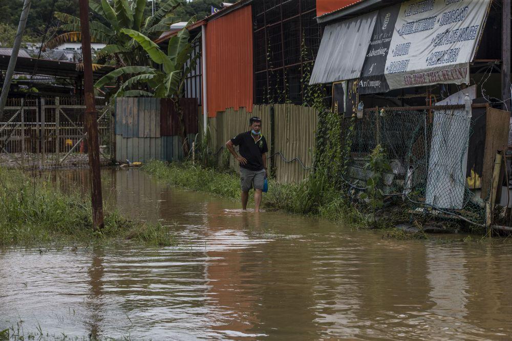 A man wades through flood waters on Jalan Datuk Panglima Banting in Penampang, Sabah September 15, 2020. — Picture by Firdaus Latif