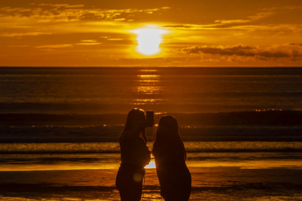 People take a picture of the setting sun on the Tanjung Aru beach in Kota Kinabalu September 30, 2020. — Picture by Firdaus Latif