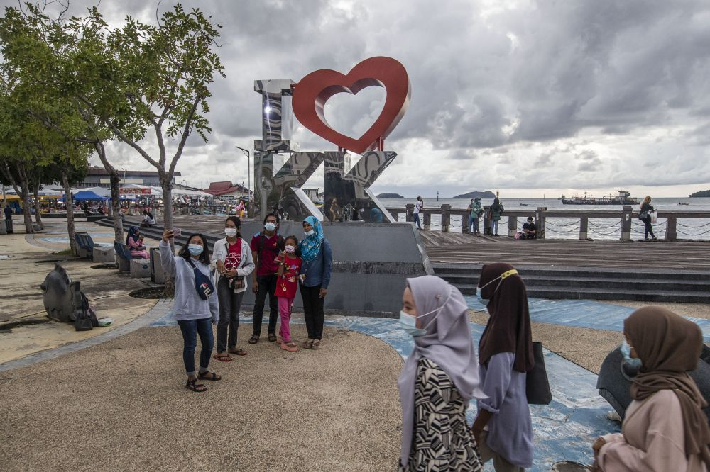 Visitors pose for pictures near the Kota Kinabalu Waterfront September 30, 2020. — Picture by Firdaus Latif