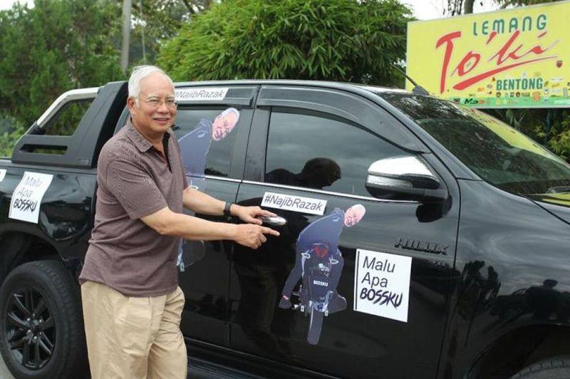 Najib points to a car emblazoned with his 'Bossku' social media persona. — Picture via Facebook/NajibRazak