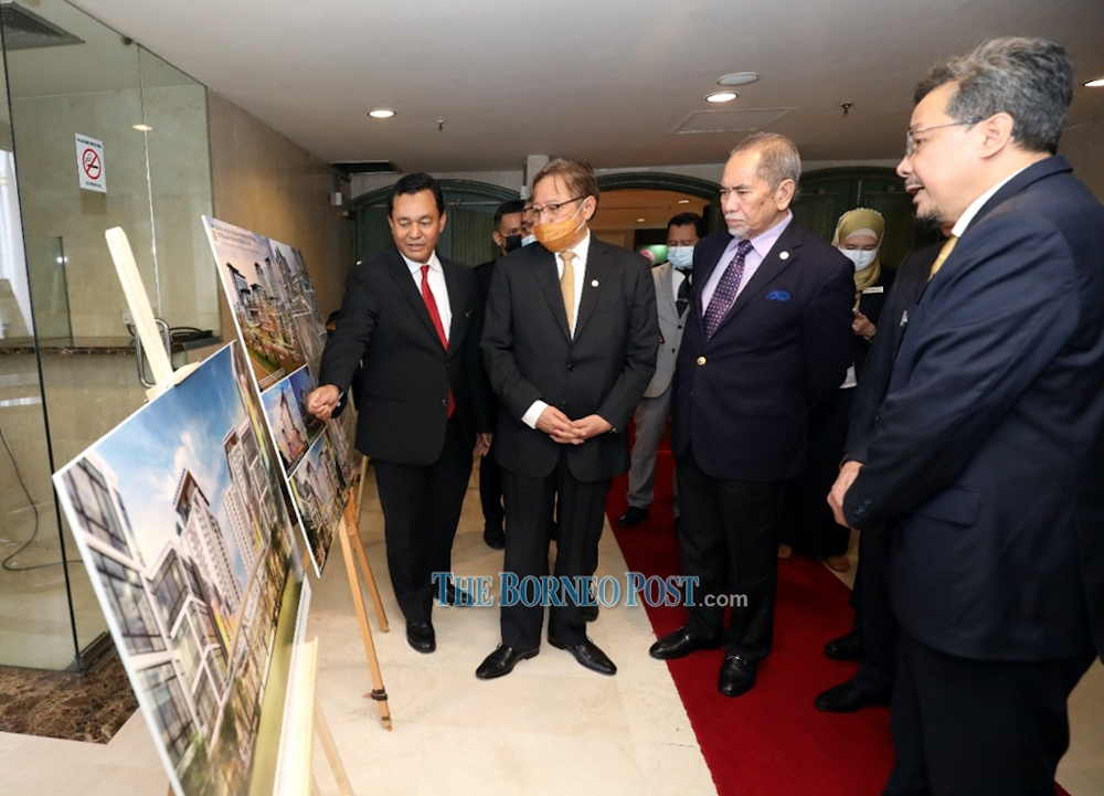 (From left) UDA Holdings Bhd chief executive officer Mohd Salem Kailany showing Abang Johari the artist rendition of the Jalan Datuk Marican Salleh project as Wan Junaidi and SEDC general manager Abdul Hadi Abdul Kadir look on. — Borneo Post pic