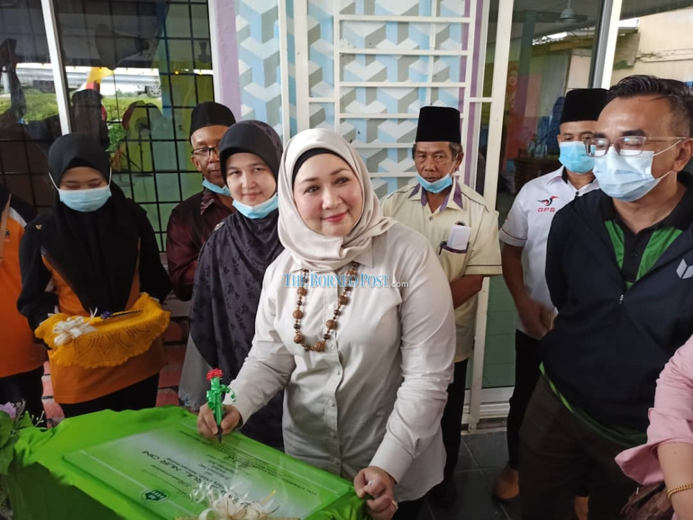 Sharifah Hasidah signing the surau plaque at the event. — Borneo Post pic