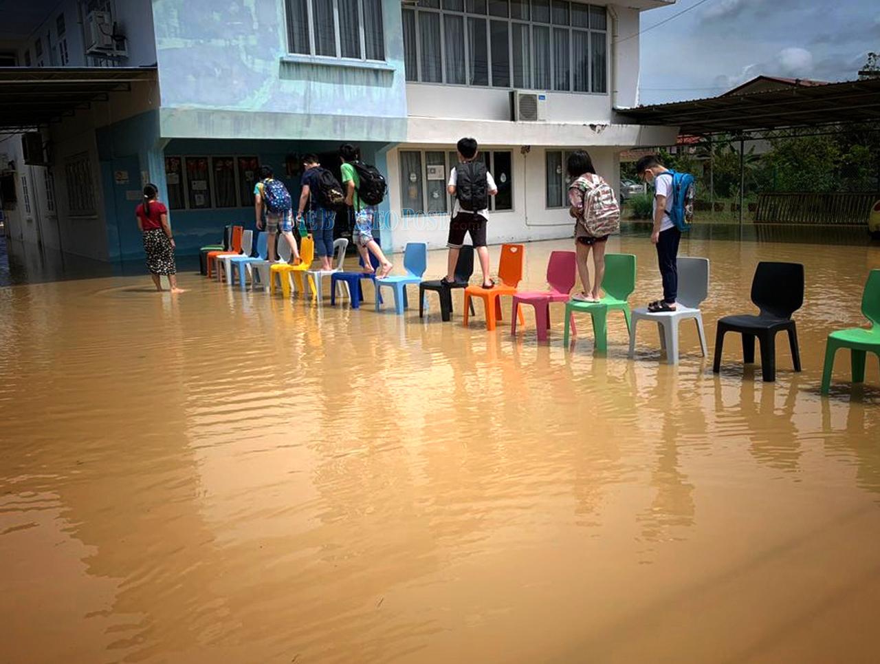 School children walk on chairs to avoid getting wet. — Picture via WhatsApp