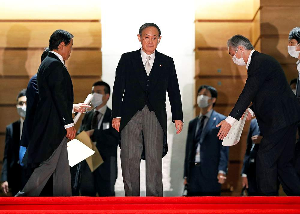 Japan's Prime Minister Yoshihide Suga prepares for a photo session with other cabinet ministers at Suga's official residence in Tokyo, Japan September 16, 2020. — Reuters pic