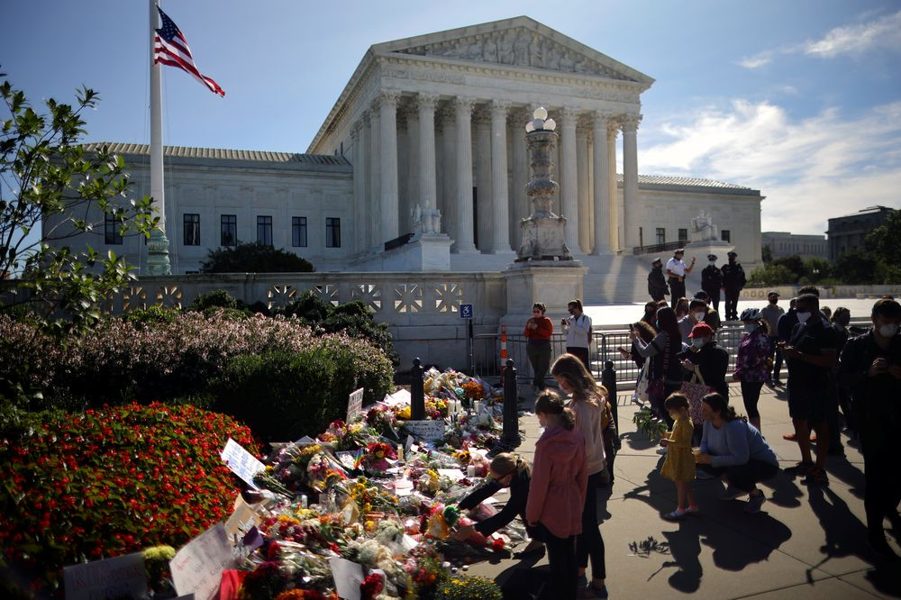 A woman puts flower on a memorial altar as people gather in front of the US Supreme Court following the death of US Supreme Court Justice Ruth Bader Ginsburg, in Washington, US, September 19, 2020. — Reuters pic