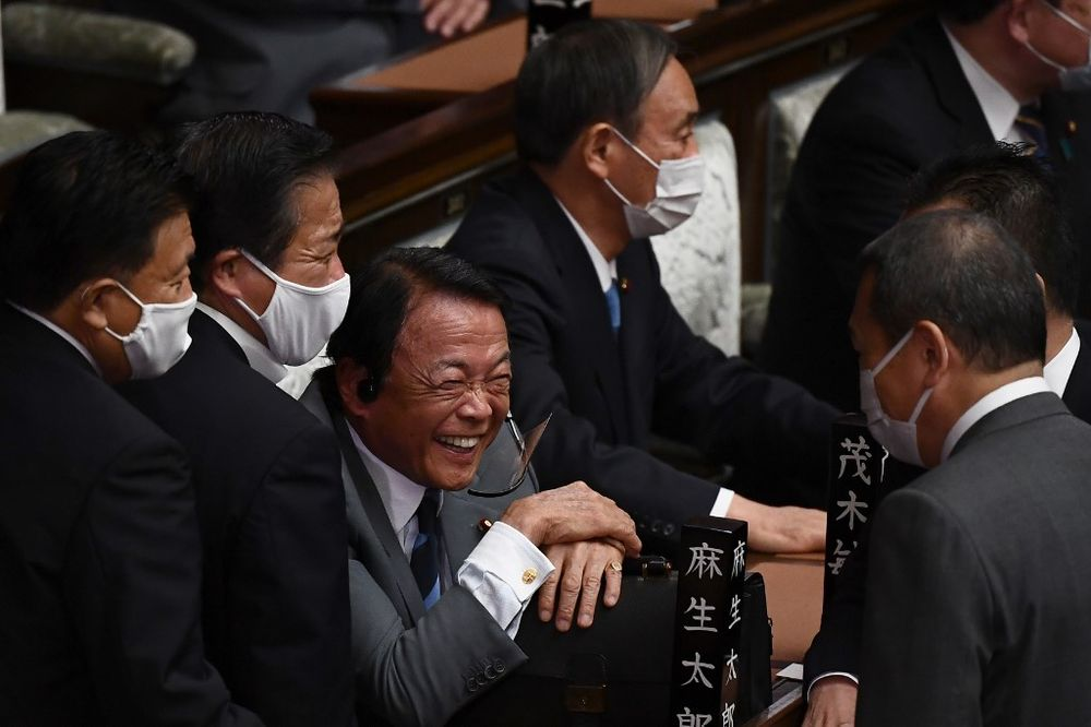 Japan's Deputy Prime Minister and Finance Minister Taro Aso (third left) shares a laugh as he sits next to the leader of Liberal Democratic Party (LDP) Yoshihide Suga (right) during a Lower House parliament session to vote for the next prime minister in Tokyo, September 16, 2020. — AFP pic