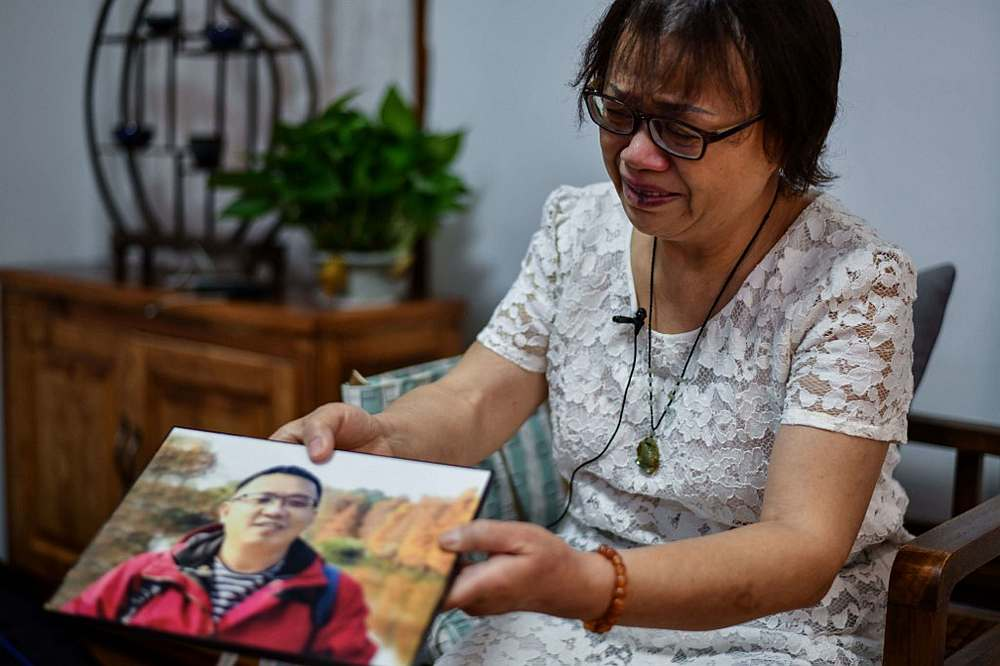 Zhong Hanneng crying as she displays a portrait of her son Peng Yi who died from the Covid-19 coronavirus in the city of Wuhan, in China's central Hubei province Sepember 6, 2020.  — AFP pic