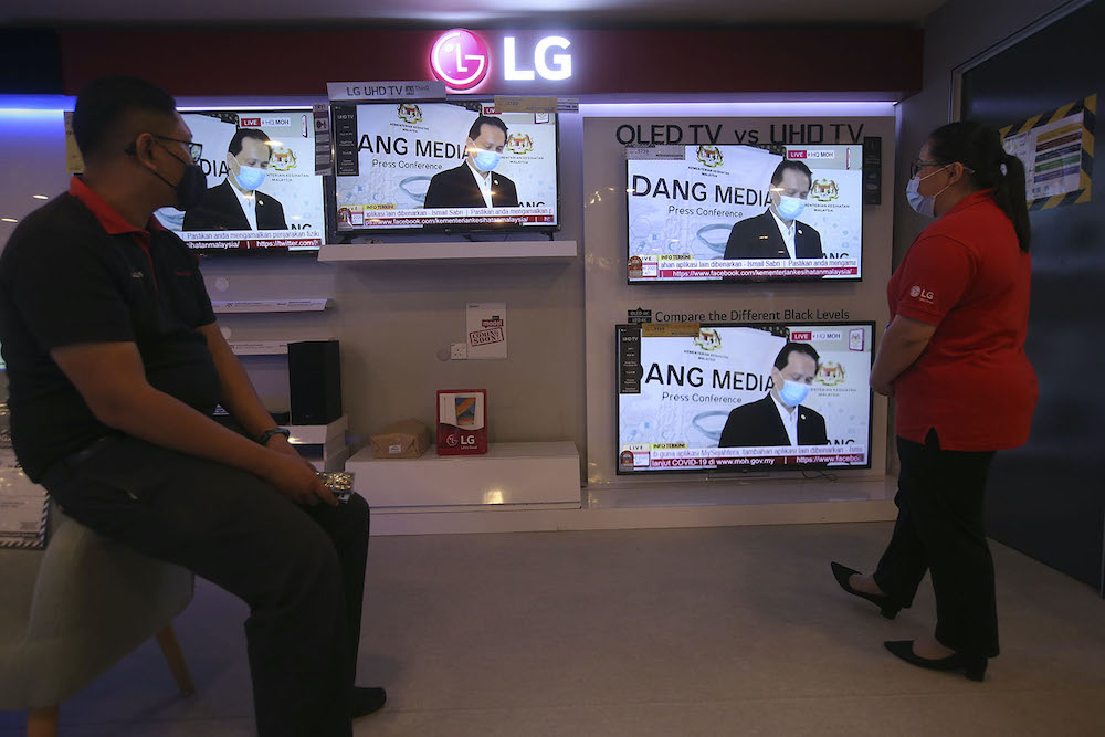 Television screens show Director General of Health Malaysia Tan Sri Dr Noor Hisham Abdullah holding a press conference from his home during his quarantine, October 6, 2020. — Picture by Hari Anggara