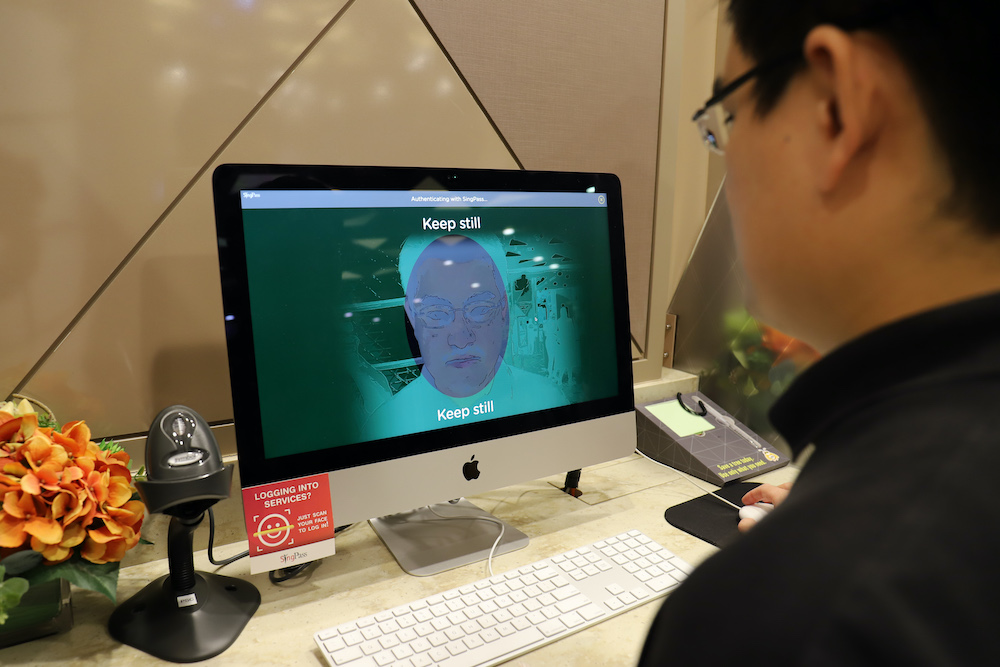 A staff member of government technology agency GovTech demonstrating the use of facial verification technology to access government services on a computer at a community centre in Singapore. — AFP pic