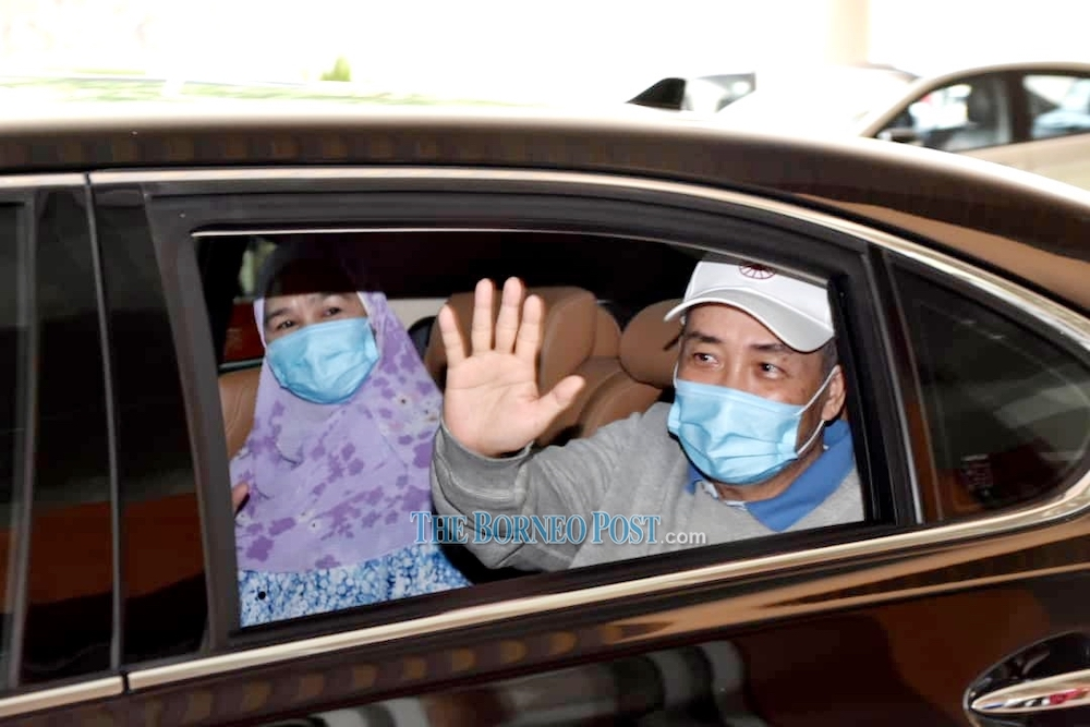 Hajiji and Julia wave to the medical personnel as they leave QEH today. — Borneo Post Online pic