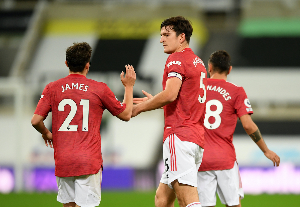 Manchester United's Harry Maguire celebrates scoring their first goal with teammates, October 18, 2020. — Pool via Reuters/Stu Forster