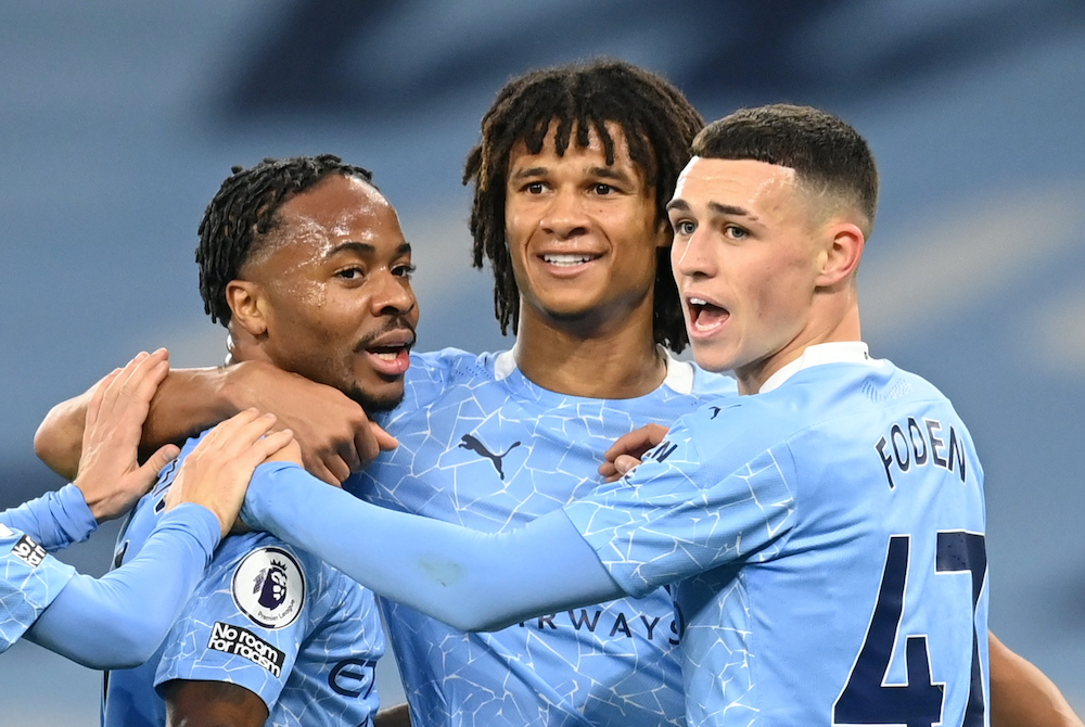 Manchester City's Raheem Sterling celebrates scoring their first goal with Phil Foden and Nathan Ake, October 18, 2020. — Pool via Reuters/Michael Regan