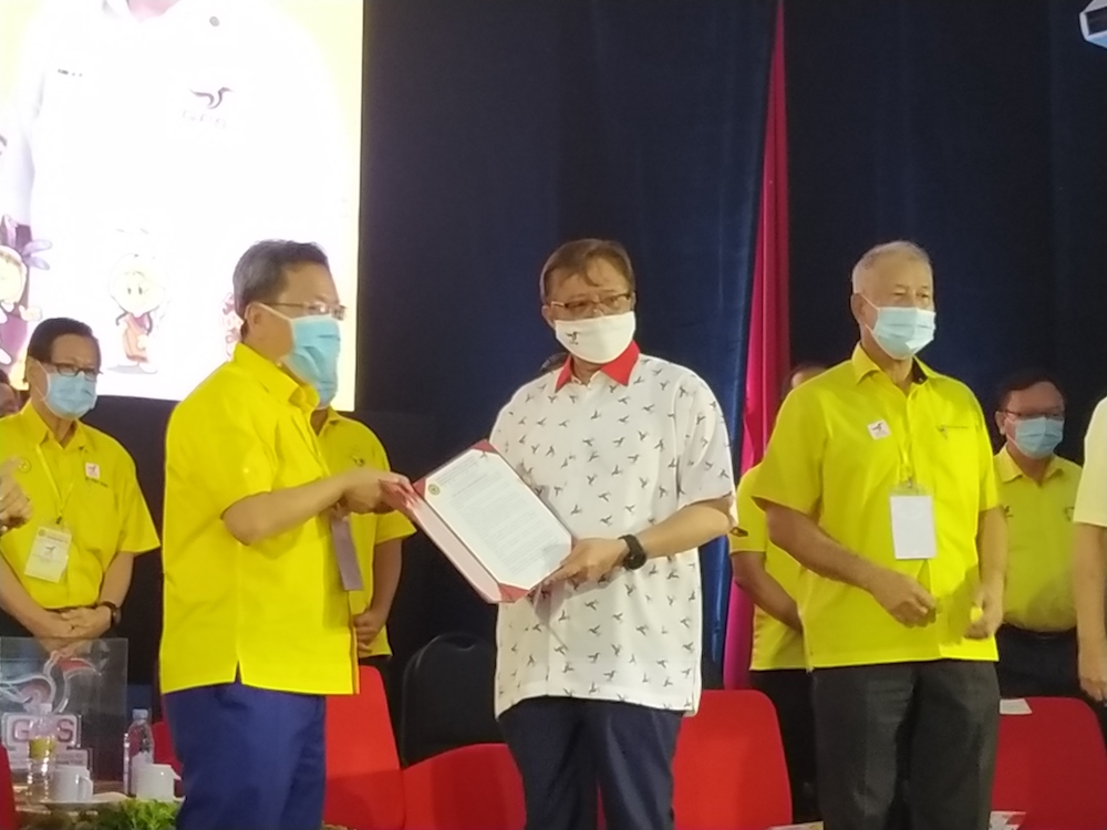 SUPP president Datuk Seri Dr Sim Kui Hian (left) hands over the party's resolutions to GPS chairman Datuk Patinggi Abang Johari Openg at the closing of SUPP's special convention in Kuching October 18, 2020. — Picture by Sulok Tawie