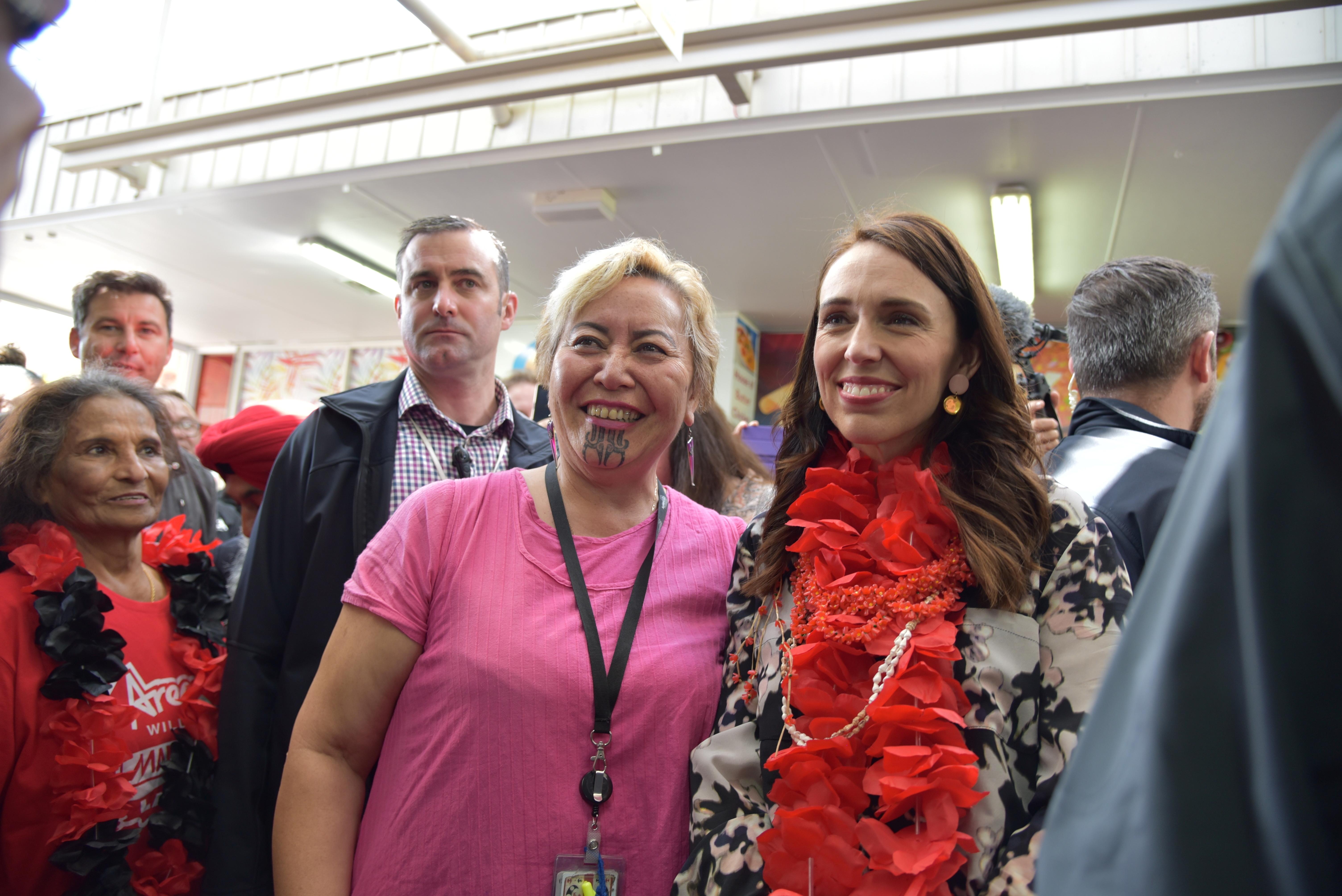 阿德恩(右)在选举前夕仍勤跑行程催票,她在奥克兰扫街受到热烈欢迎,有人伸手拥抱她,有人抢着与她自拍合照。-路透社-