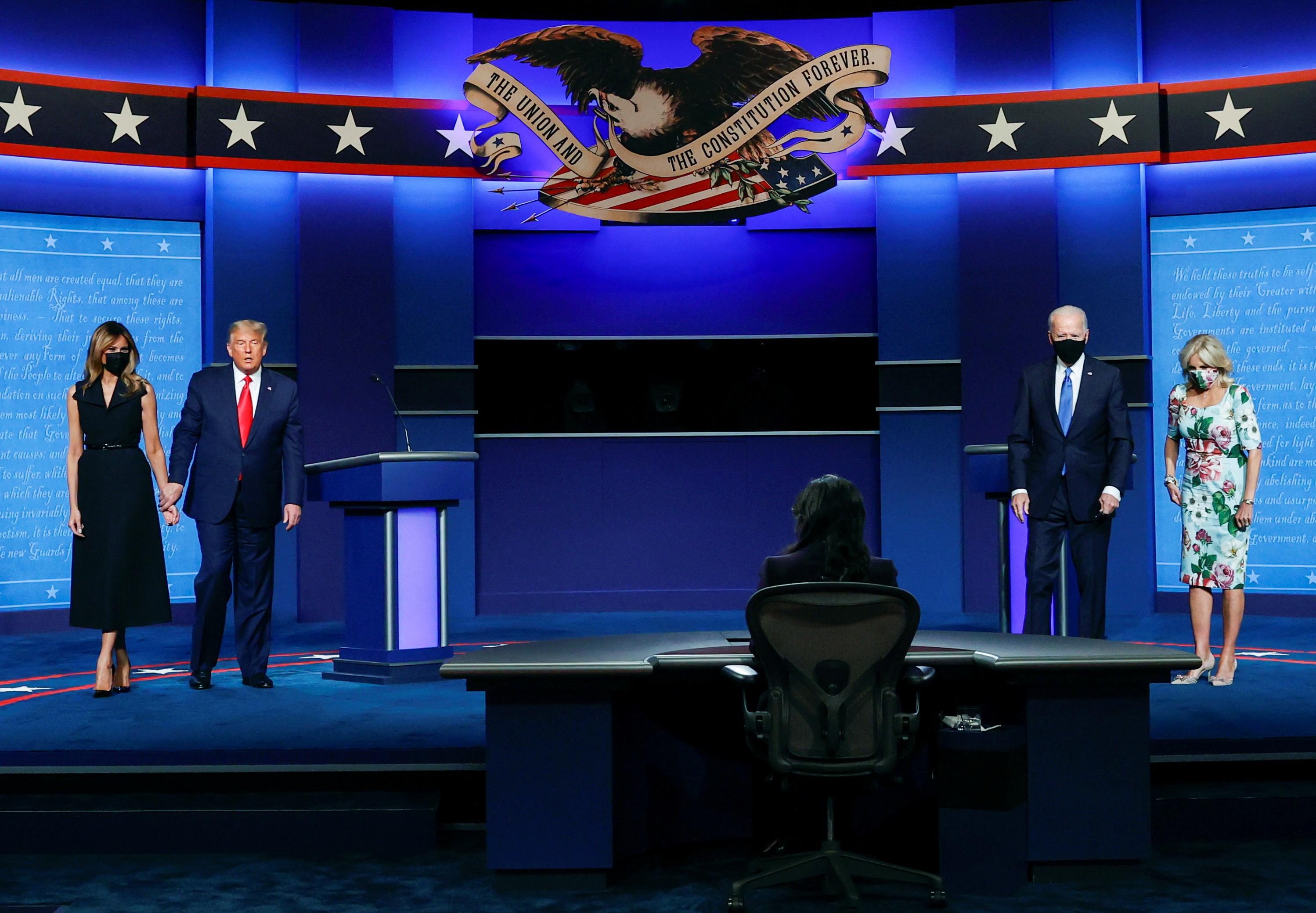 辩论会结束后,梅拉妮亚(左1)和拜登(右2)妻子吉尔(右1)都上台向各自的丈夫表达支持,直到电视台直播画面结束时,4人中只有特朗普(左2)没戴口罩,形成强烈对比。-路透社-