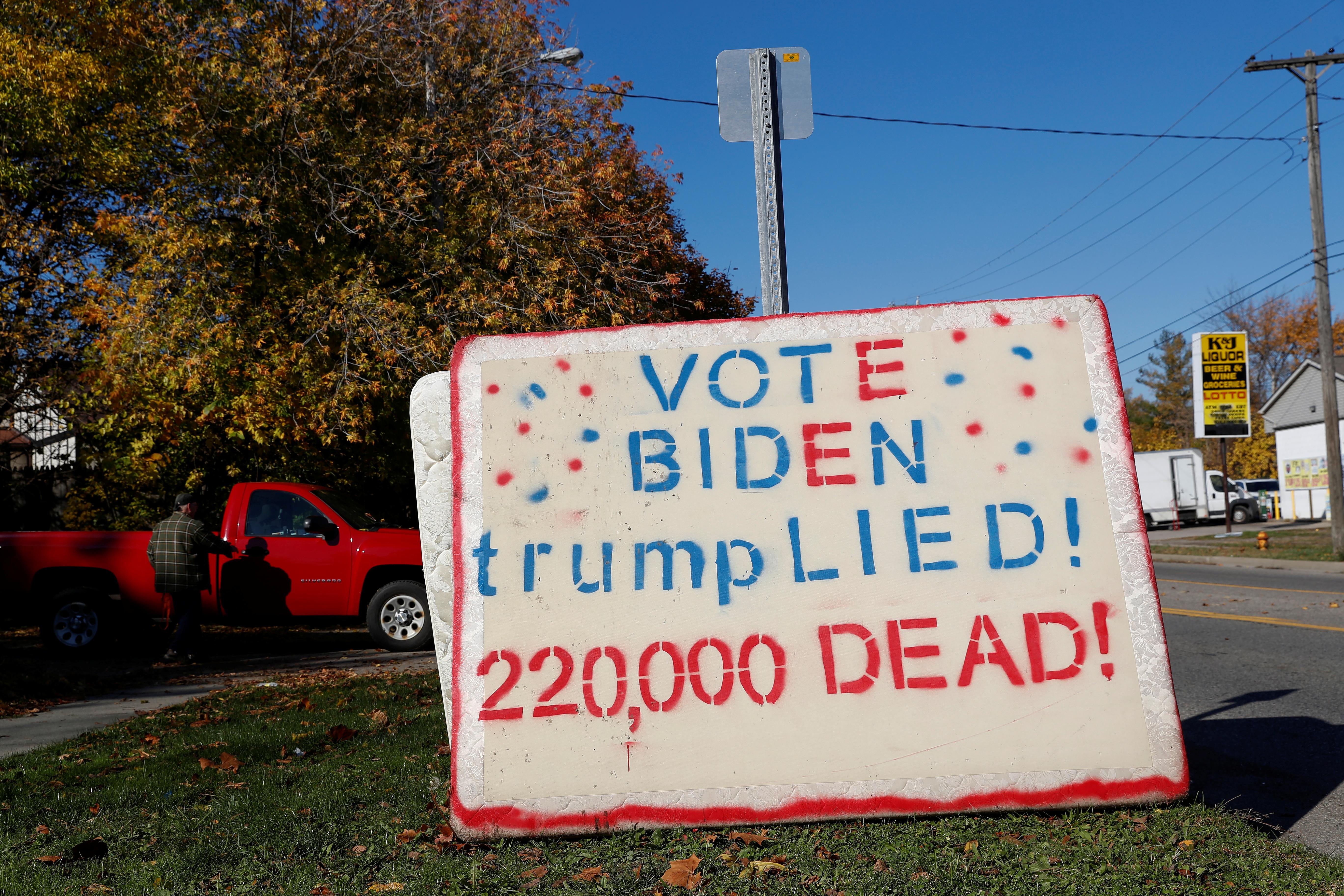"""不满特朗普政府抗疫表现的密歇根州居民,在住处外竖立写着""""投拜登  特朗普说谎  22万人死""""的标语牌。-路透社-"""