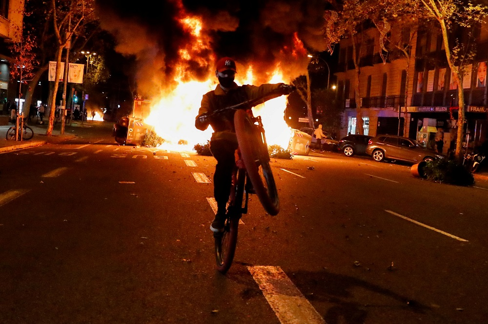A person rides a bicycle in front of a fire during a protest against the closure of bars and gyms, amidst the coronavirus disease outbreak, in Barcelona October 30, 2020. — Reuters