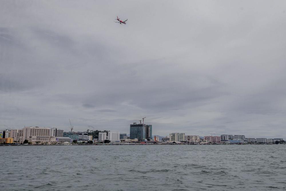 An AirAsia plane flies over the skyline of Kota Kinabalu September 30, 2020. — Picture by Firdaus Latif