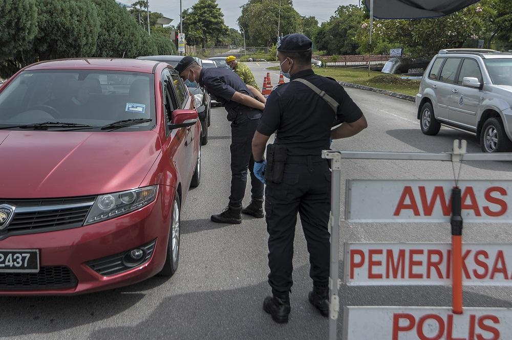 Policemen conduct checks on vehicles at a roadblock at Taman Sri Andalas in Klang October 10, 2020. — Picture by Shafwan Zaidon