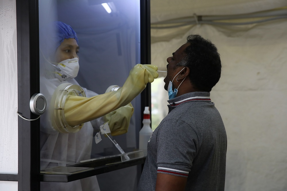A health worker inside a protective chamber collects swab samples to test for Covid-19 at the Sunway Medical Centre in Subang Jaya October 15, 2020. — Picture by Yusof Mat Isa