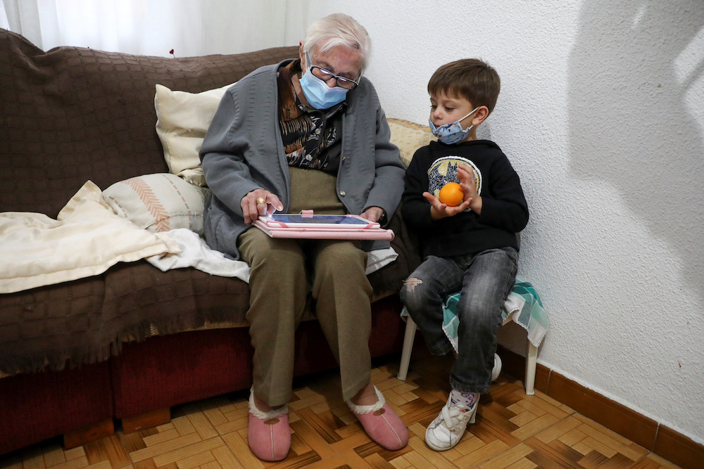 Florentina Martin, a 99 year-old woman who survived coronavirus disease (Covid-19), plays a digital puzzle with her great-grandson Pedro Valle near Madrid, Spain, October 20, 2020. — Reuters pic