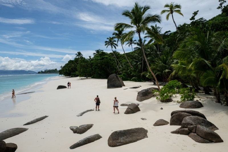 Tourists walking on the beach with granite rocks on Silhouette Island, the third largest island of Seychelles. — AFP pic