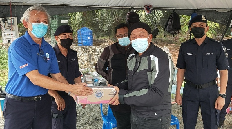 Sabah police commissioner Datuk Hazani Ghazali (right) receiving a contribution on behalf of the security personnel manning the roadblock at Mile 2, Apas Road yesterday. Hazani is on a statewide tour to inspect all 57 roadblocks in Sabah. — Borneo Post Online pic
