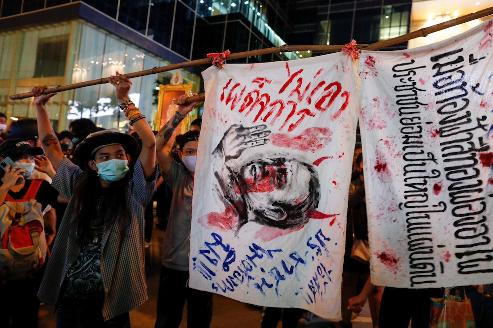 A pro-democracy demonstrator holds signs on a stick during a protest, in Bangkok, Thailand October 26, 2020. — Reuters pic
