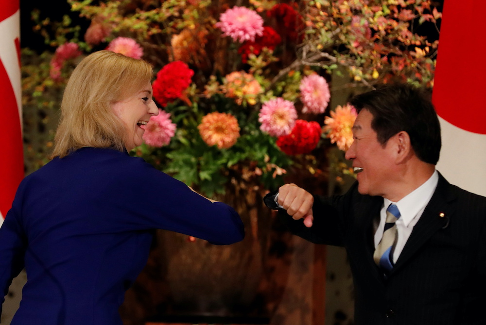 Britain's International Trade Secretary Elizabeth Truss and Japanese Foreign Minister Toshimitsu Motegi bump elbows following a signing ceremony of the UK-Japan Comprehensive Economic Partnership Agreement in Tokyo, Japan October 23,2020. — Reuters pic