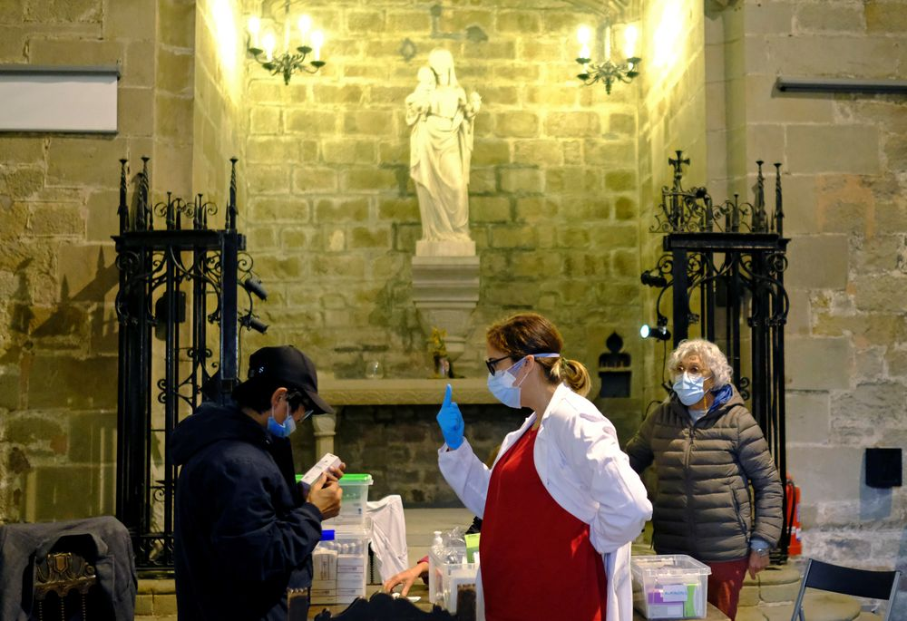 A man receives medical treatment from Merce Lopez, 42, who is a volunteer doctor doing health check-ups for people suffering economic hardship inside Santa Anna Church, in Barcelona, Spain October 29, 2020. — Reuters pic