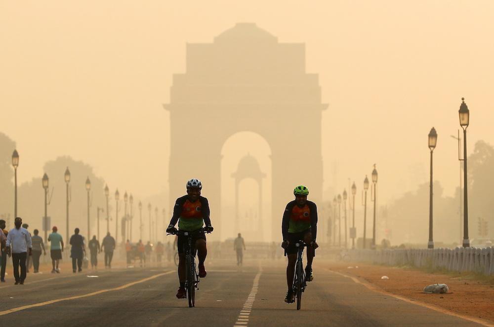 Männer fahren mit ihren Fahrrädern vor dem in Smog gehüllten India Gate in Neu-Delhi, Indien, am 24. Oktober 2020. - Reuters Bild