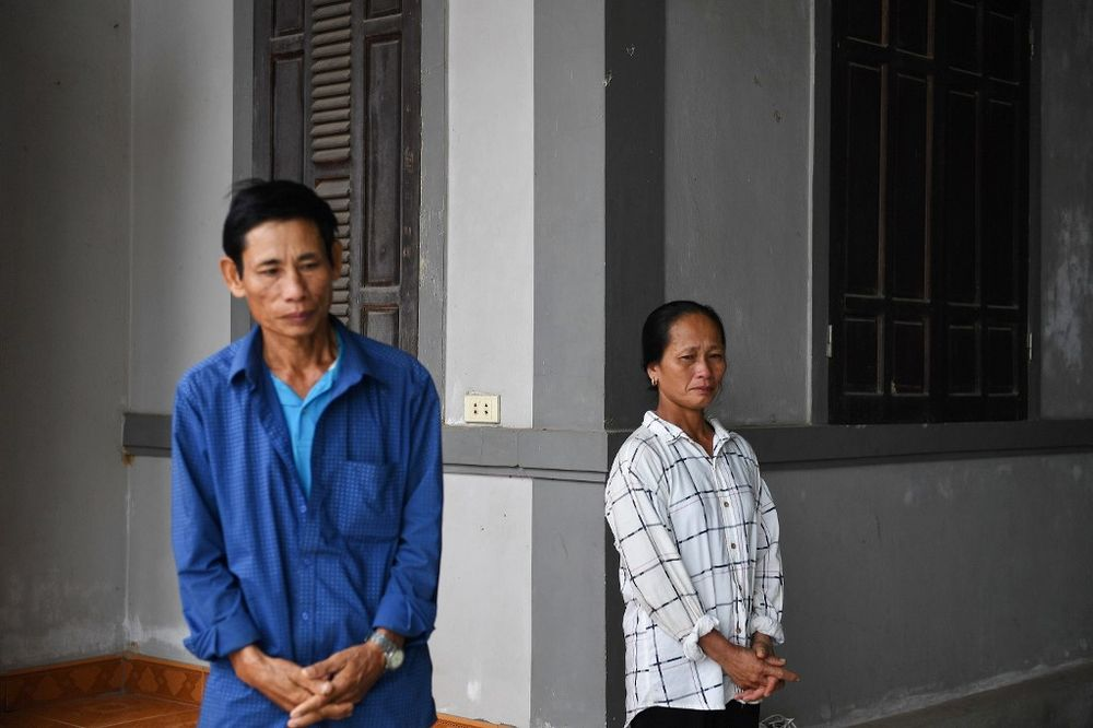 This photograph taken on October 11, 2020 shows parents of the late 20-year-old Nguyen Dinh Luong, who was among the 39 people found dead in a truck in Britain last year, standing in a courtyard at their house in Can Loc district of Vietnam's Ha Tinh province. — AFP pic