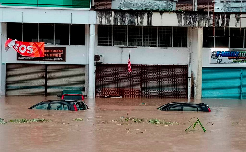 A few vehicles are seen submerged in flood water in Tuaran October 5, 2020. — Bernama pic