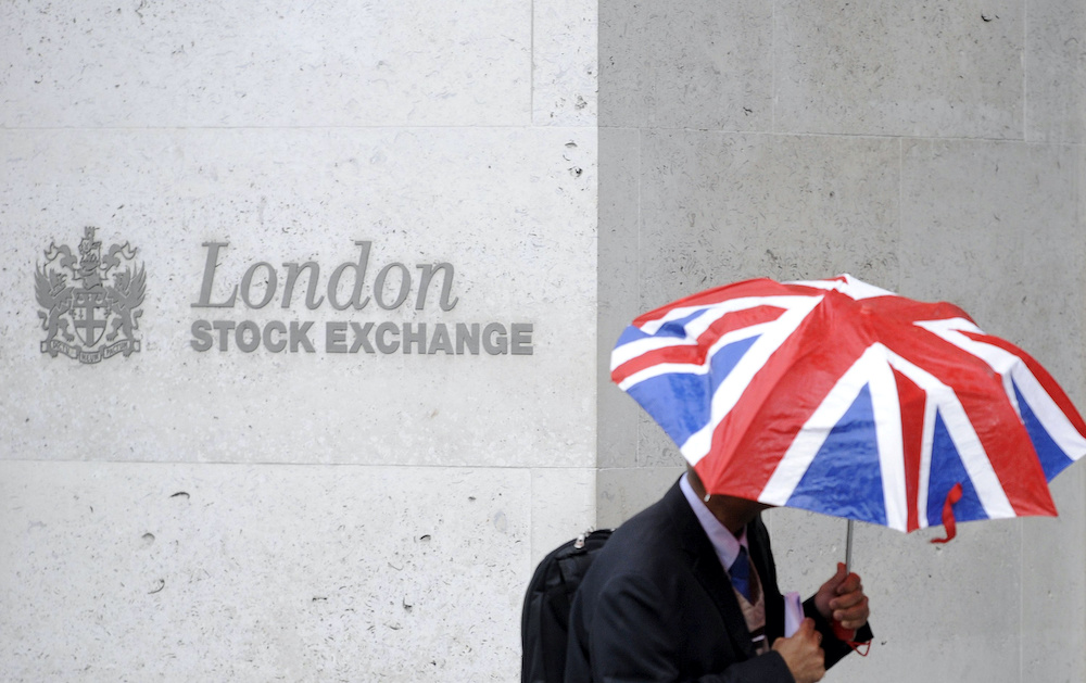 File photo of a worker sheltering from the rain as he passes the London Stock Exchange in the City of London at lunchtime October 1, 2008. ― Reuters pic