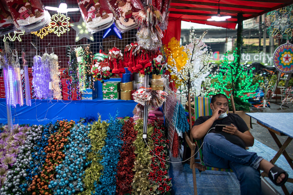 A vendor of Christmas ornaments keeps his mask on his chin to smoke a cigaratte at a market amid the coronavirus disease pandemic in Quezon City, Metro Manila, Philippines, October 14, 2020. ― Reuters pic