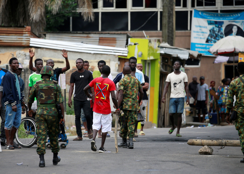 Military personnel move towards people standing along a blocked road in Ikeja, as Nigeria's Lagos state remains under curfew, Nigeria October 23, 2020. — Reuters pic