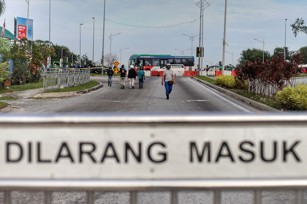 Members of the public opt to walk to their places of work after the police blocked the entrance to Persiaran Sungai Buloh as the conditional control movement order kicks in on October 14 2020. — Picture by Ahmad Zamzahuri