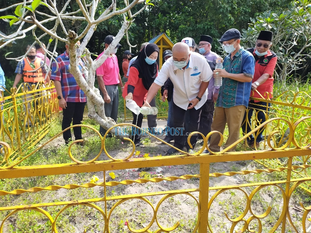 Miri mayor Adam Yii (3rd right) pouring 'air mawar' on the Datuk Permaisuri's grave during his visit to Makam Permaisuri October 7, 2020. — Borneo Post pic