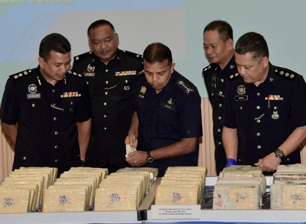 Johor police chief Datuk Ayob Khan Mydin Pitchay (centre) looking at seized drugs on display at the Johor police contingent headquarters in Johor Baru today. — Picture by Ben Tan