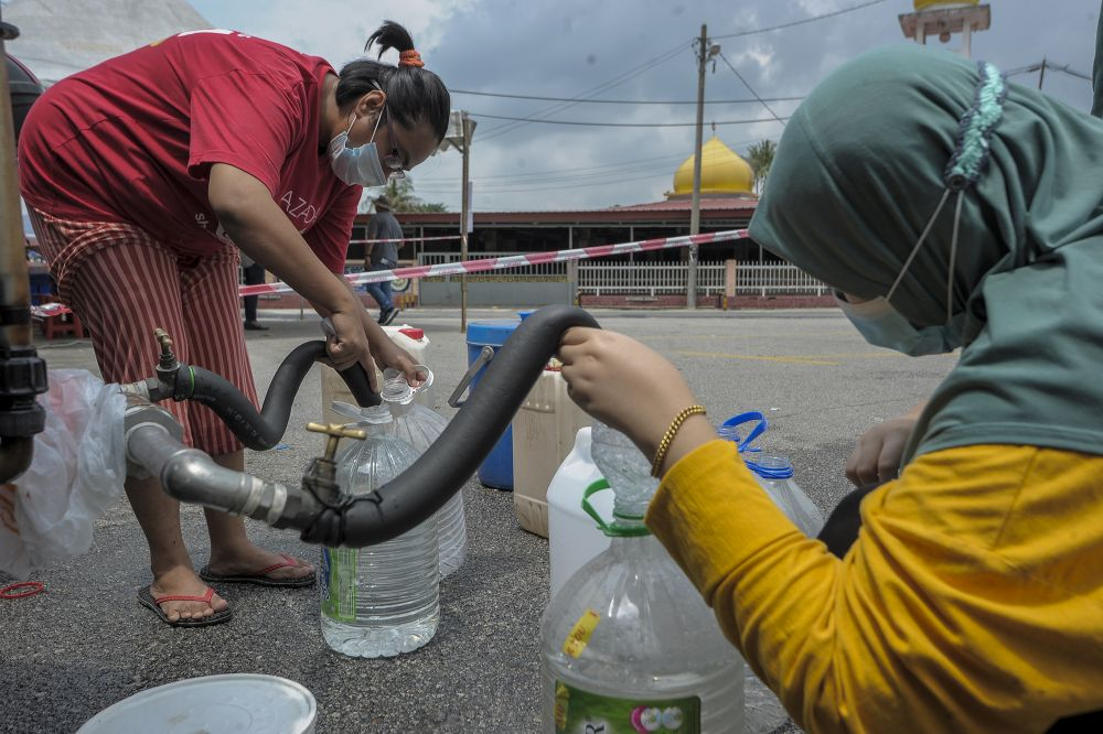Residents fill their pails at a water point in Bangi following the water disruption in Hulu Selangor October 6, 2020. ― Picture by Shafwan Zaidon