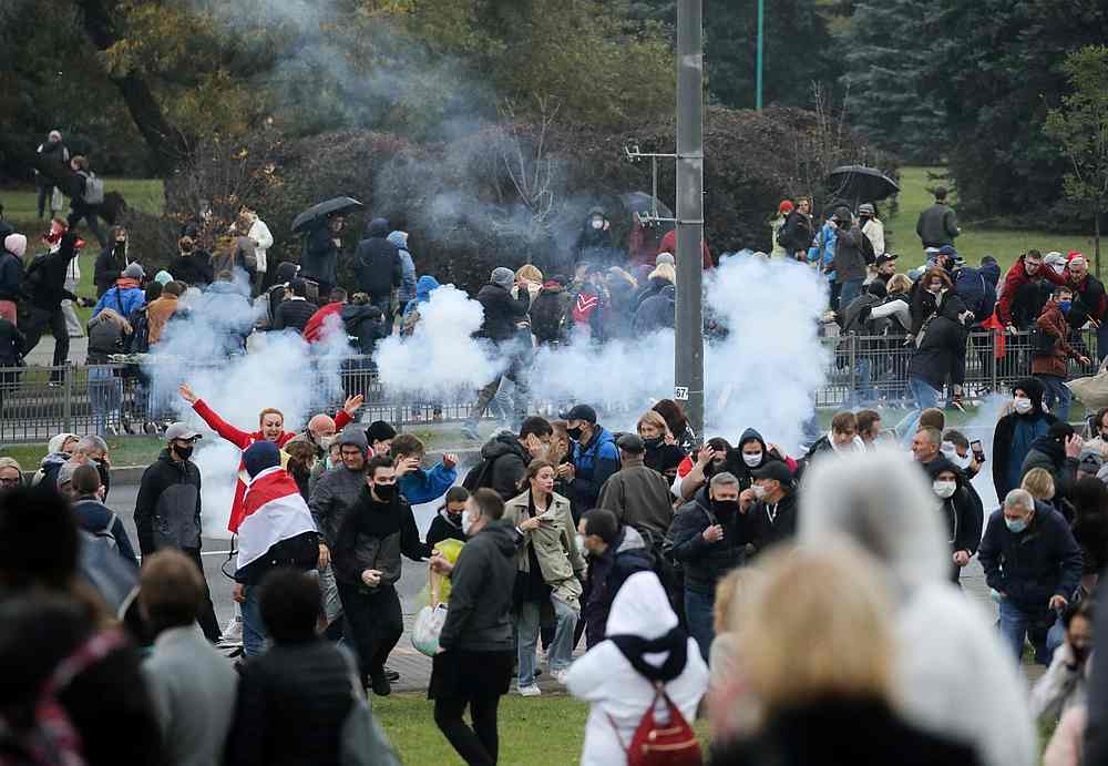 Demonstrators react as a stun grenade explodes during an opposition rally to reject the presidential election results in Minsk, Belarus October 11, 2020. — BelaPAN pic via Reuters