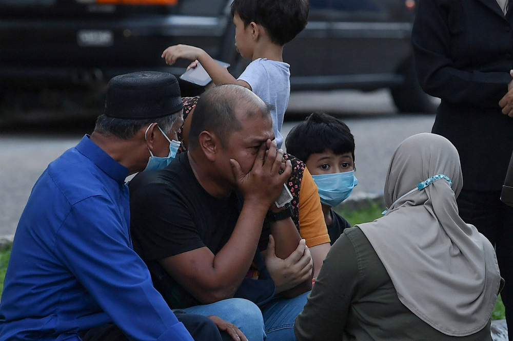 Mohamad Aryan Difa Danish Mohd Azizul's father Mohd Azizul Mohamad, 35, (2nd left) is seen with family members outside the Sultanah Nur Zahirah Hospital October 25, 2020. — Bernama pic