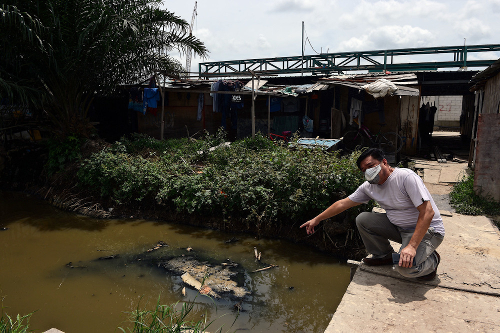 A resident points to the waste dumped into Sungai Manggis October 17, 2020. — Bernama pic