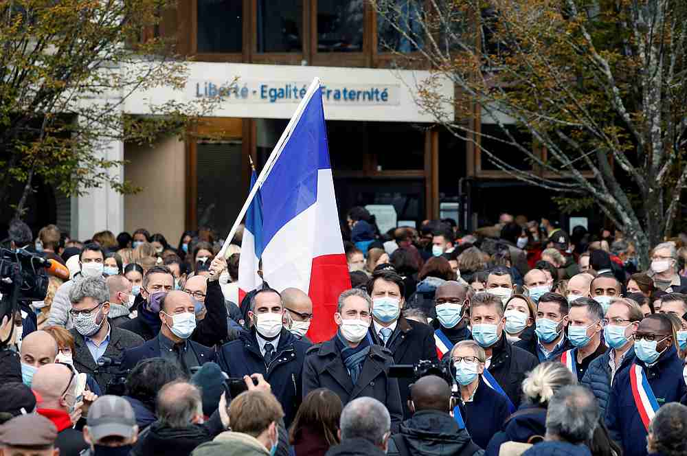 People gather in front of the Bois d'Aulne college after the attack in the Paris suburb of Conflans St Honorine, France October 17, 2020. — Pool pic via Reuters