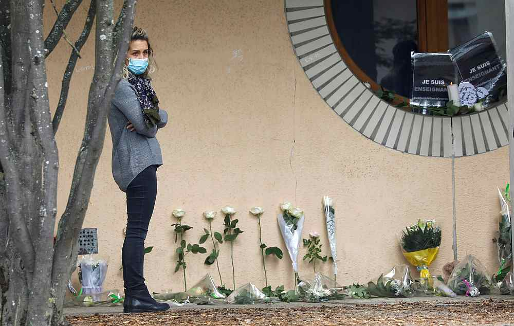 A woman stands next to flowers at the Bois d'Aulne college after the attack in the Paris suburb of Conflans St Honorine, France October 17, 2020. — Reuters pic