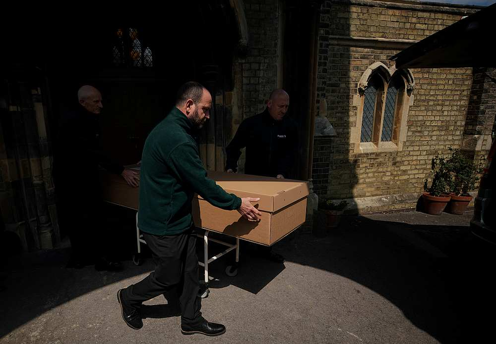 Mortuary workers push a coffin containing the body of a person who died of Covid-19 to a hearse at Poppy's Funerals in Lambeth Cemetery, in London, Britain May 4, 2020. — Reuters pic