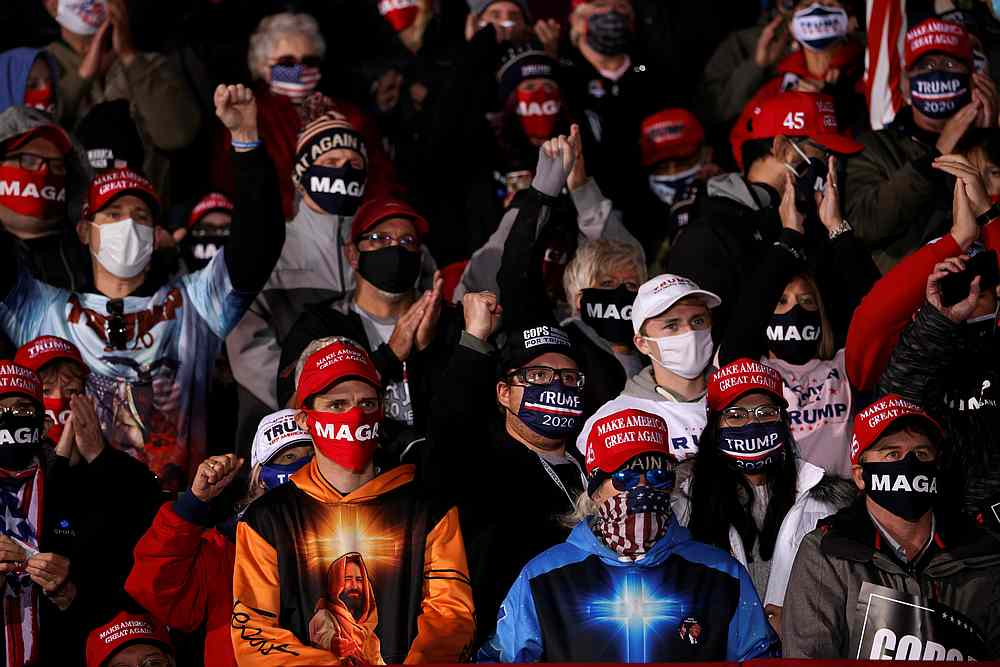 Attendees wearing face masks listen as US President Donald Trump holds a campaign rally at Southern Wisconsin Regional Airport in Janesville, Wisconsin October 17, 2020. — Reuters pic